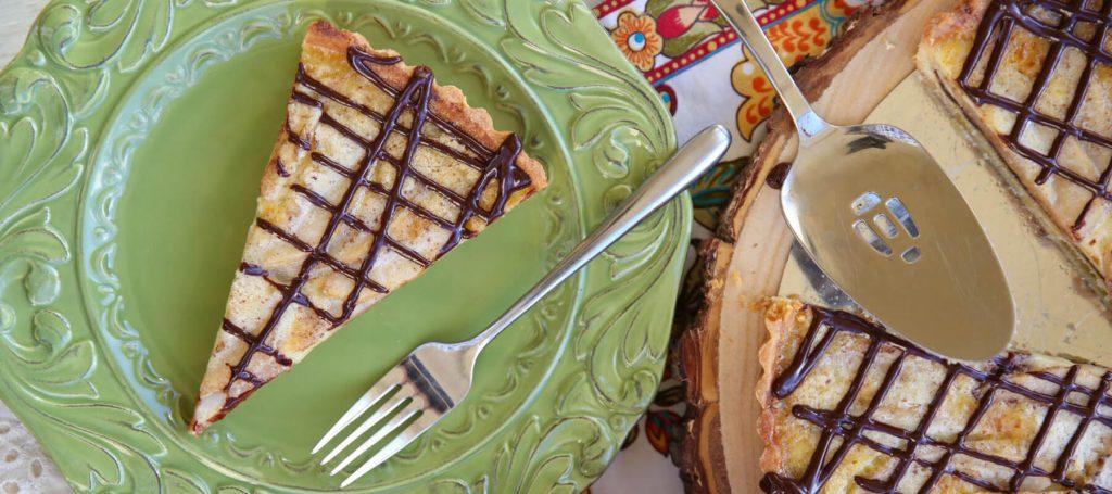 a slice of chocolate custard pear tart on a green plate