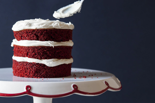 a layered red velvet cake on a cake stand being frosted with vanilla buttercream frosting
