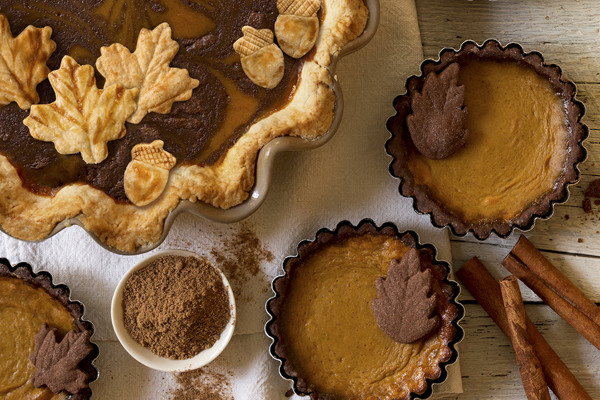 a chocolate pumpkin pie with cinnamon and pastry acorns