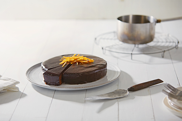 a sachertorte with apricots on a big white plate next to a knife and some other silverware