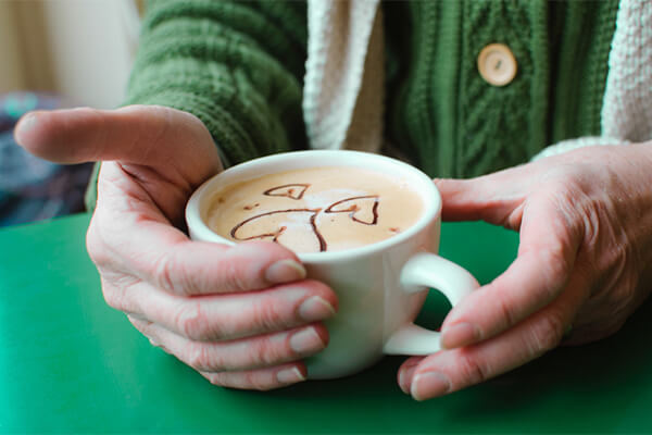 A woman's hands holding a latte with heart designs sprinked on top with cocoa powder