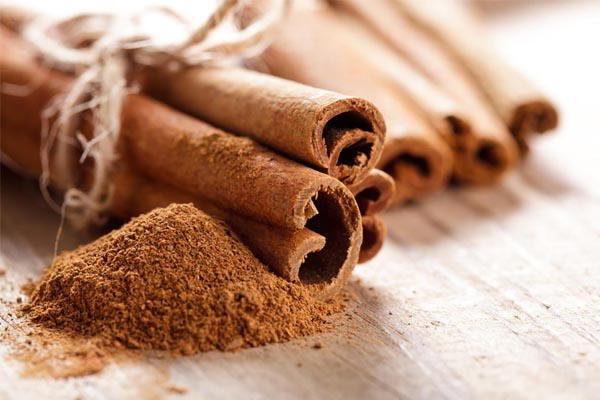 Sticks of cinnamon up close with a pile of grated cinnamon next to it