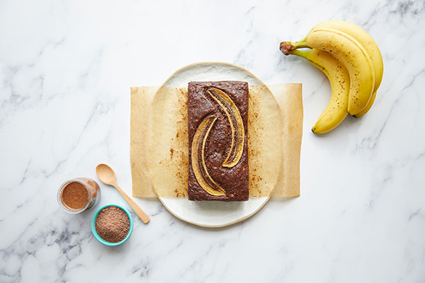 A small loaf of banana bread with a bunch of bananas on a marble table