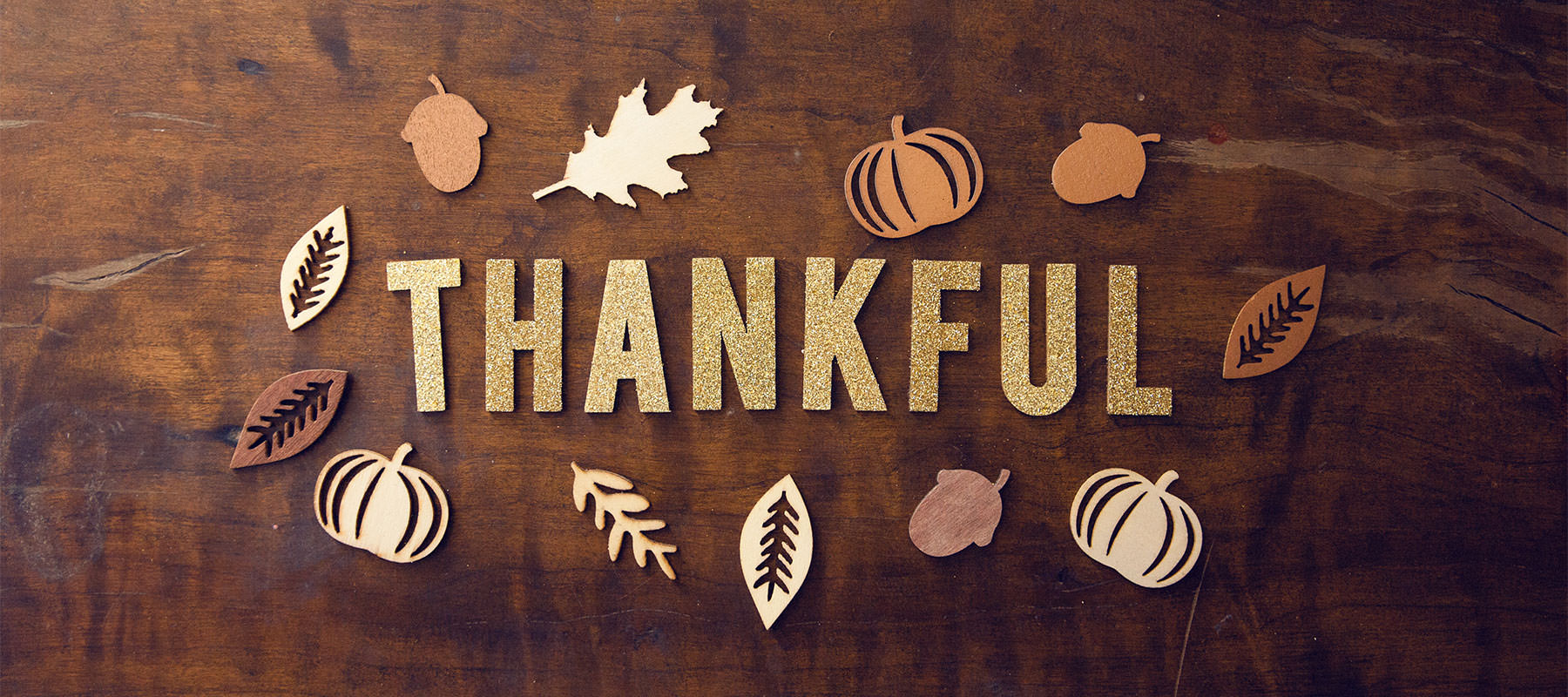 thankful spelled out on a table with leaf decals