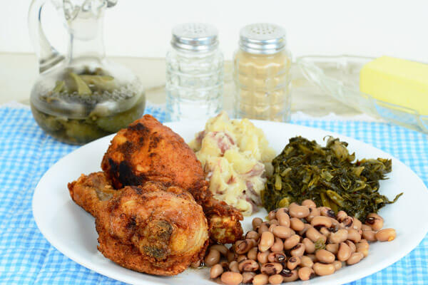 soul food meal on a white plate with a blue tablecloth