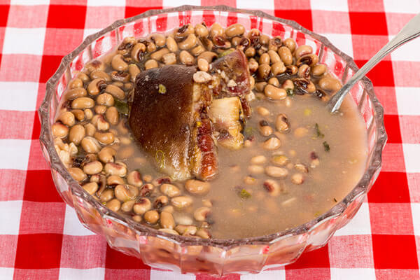 bowl of black eyed peas with ham hock on a checkered tablecloth