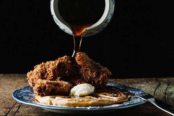 chicken and waffles with syrup being poured over the top