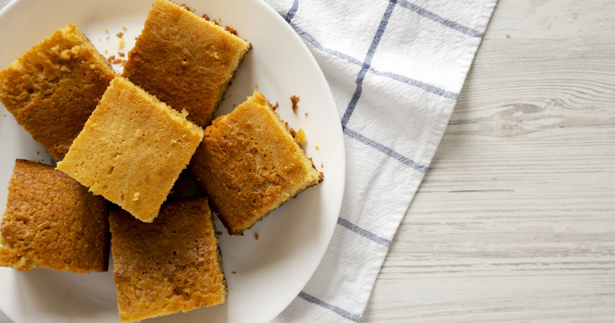 sliced cornbread on a white plate and checkered napkin