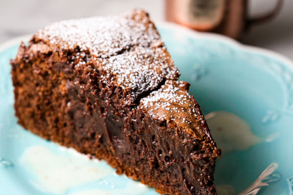 A slice of chocolate gateau cake with powdered sugar topping