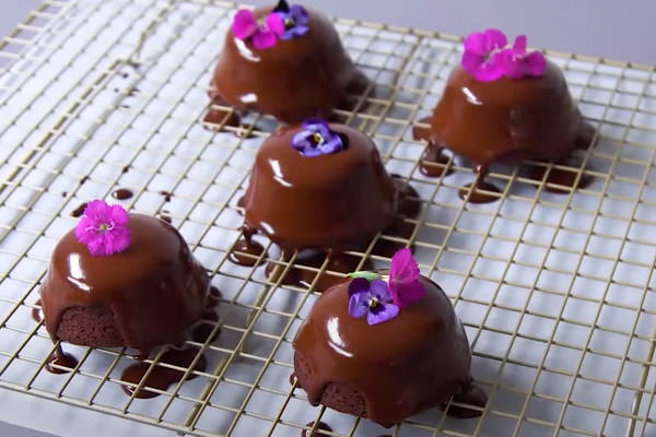 Chocolate ganache brownies with chocolate glaze and edible pink and purple flowers